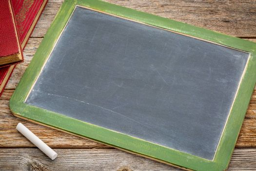 blank slate blackboard with a white chalk and a stack of books against rustic wooden table