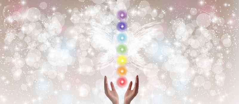 Healing Hands and seven chakras on a sparkling pastel coloured background