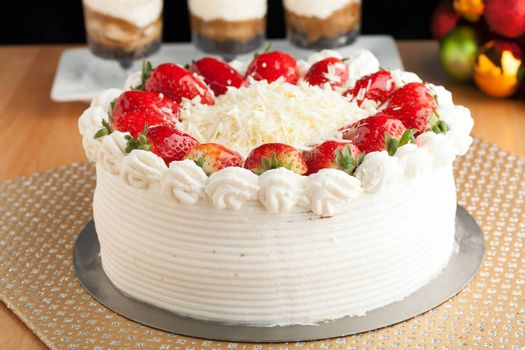 Top view of an entire strawberry shortcake with white chocolate shavings.