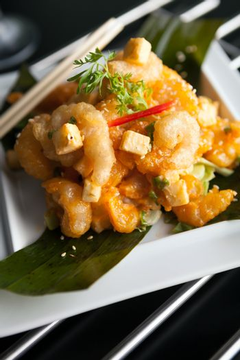 Thai crispy shrimp dish with apple and sesame seeds presented beautifully on a white square plate with chopsticks.