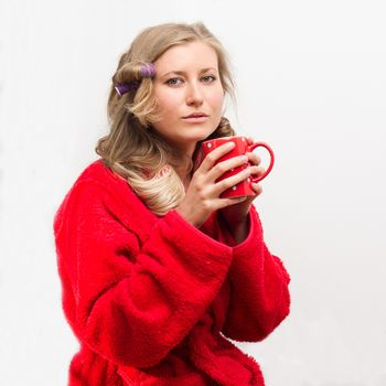 Half-length portrait pretty young housewife wearing curlers and  wrapper holding cup of tea
