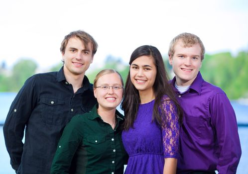 Four young multiethnic friends standing  together outdoors