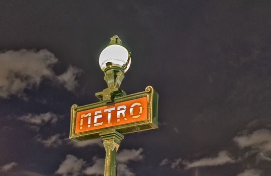 Parisian metro sign Paris France at night