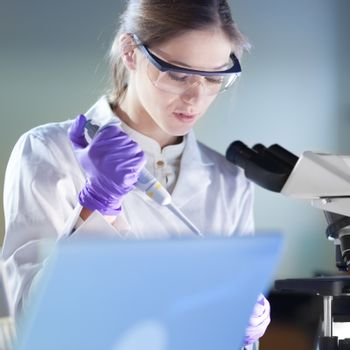 Life scientist researching in laboratory. Portrait of attractive, young, confident female health care professional pipetting under microscope in hes working environment. Healthcare and biotechnology.