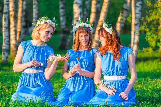 girlfriends with wreaths on their heads, sitting on a green mead