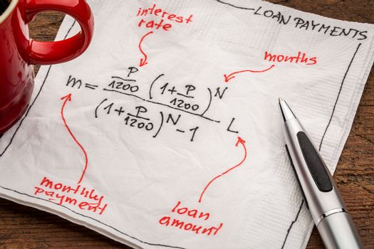 loan payment equation sketched on a white napkin with a cup of coffee