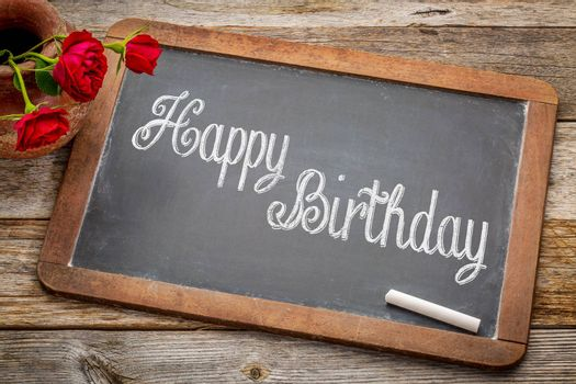 Happy Birthday greetings  - white chalk text on a vintage slate blackboard with red roses against rustic wood