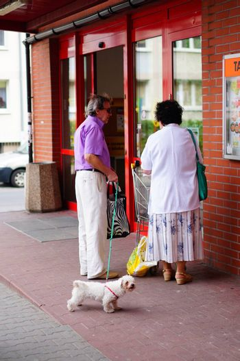 POZNAN, POLAND - SEPTEMBER 13, 2014: Man and woman standing with dog in front of a supermarket
