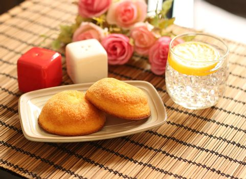 muffin cakes and cold lemonade with ice placed on wooden