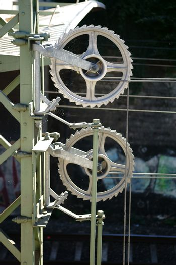 The close-up of gears of a wire tensioning device on a railway line.