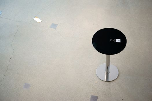 A round bar table stands on a markedly cracked floor.
