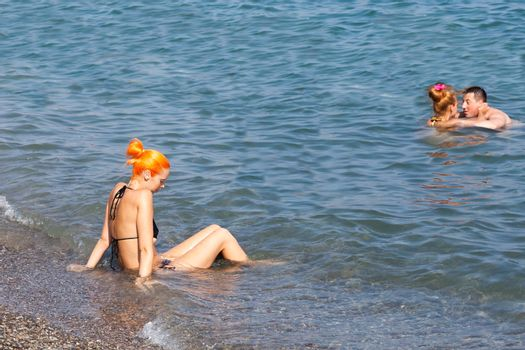 ALUSHTA,RUSSIA-September 06:beautiful the girl sits on the seashore,RUSSIA-SEPTEMBER 06 2015.In the Crimea many people sunbathe on the bank of the Black Sea
