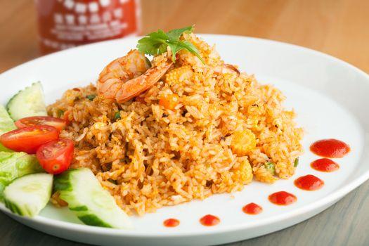 Sriracha shrimp fried rice dish with garnish dots of siracha sauce.