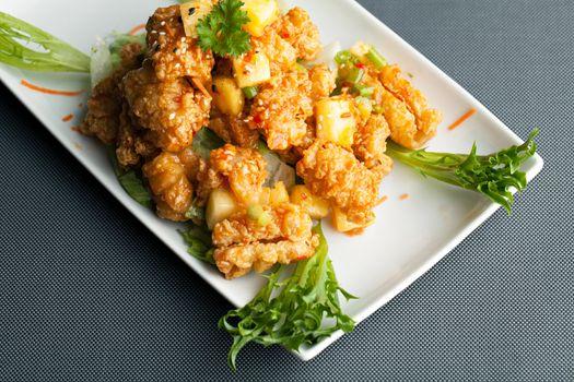 Thai fried calamari appetizer garnished with fresh pineapple chunks.