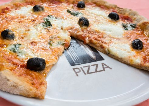 wheat pizza with olives and basil