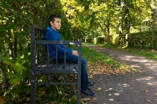 The photo depicts a boy sitting on a bench