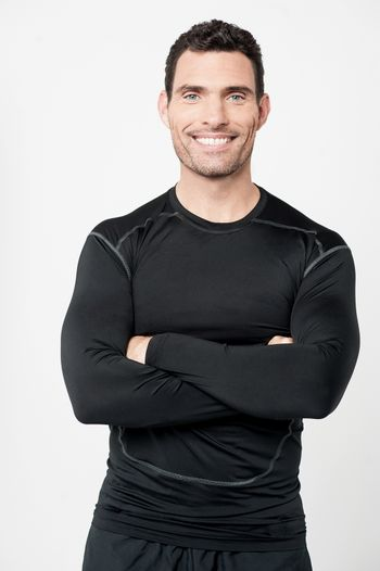 Happy male athlete with folded arms