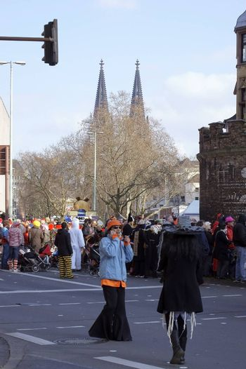 Cologne, Germany - March 02, 2014: In a street of Cologne celebrating colorfully dressed people the carnival with the Cologne Cathedral in the background on March 02, 2014 in Cologne.