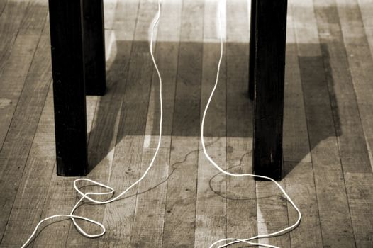 A telephone stand on an old wooden floor casts a shadow square.