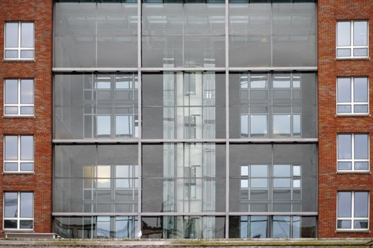 A modern apartment building with a glass facade and brick stones.