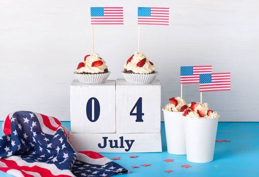 greeting card on the Independence Day of America, two cupcakes, two desserts with cream, strawberries and American flags, perpetual calendar with the words Jule 4 on a white and blue background