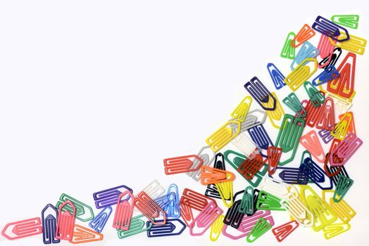 Close-up of multi-colored paper clips on a white background.