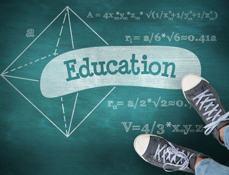 The word education and casual shoes against green chalkboard