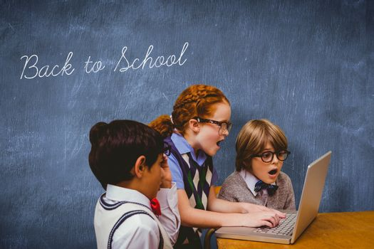 The word back to school and pupils using laptop against blue chalkboard