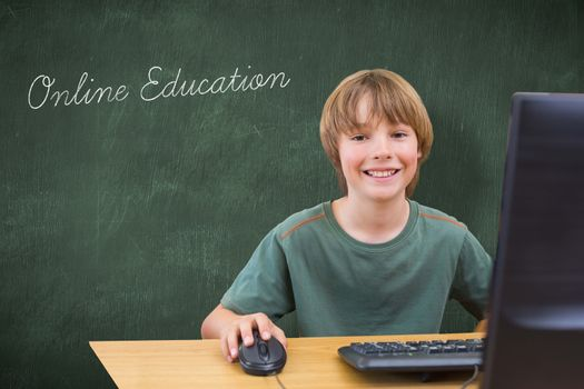 The word online education and school kid on computer against green chalkboard