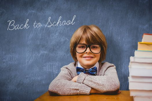The word back to school and pupil with many books against blue chalkboard