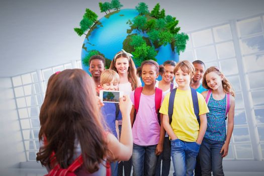 Cute pupils using mobile phone  against globe floating in room