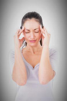 Composite image of brunette suffering from migraine