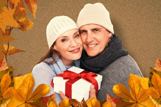 Composite image of casual couple in warm clothing holding gift