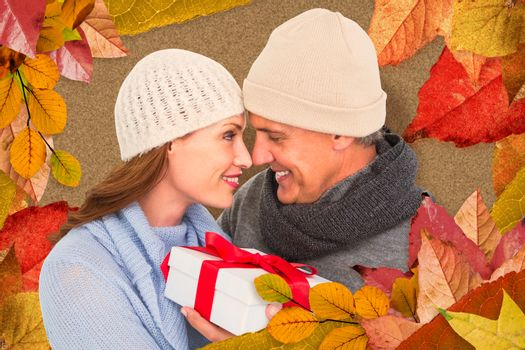 Casual couple in warm clothing holding gift against autumn leaves pattern