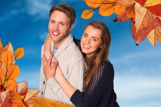 Portrait of happy young couple against blue sky
