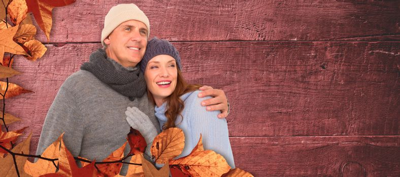 Couple in warm clothing embracing against overhead of wooden planks
