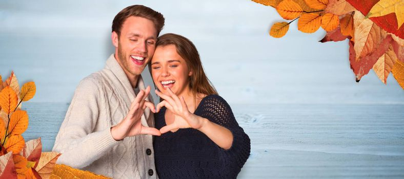 Happy couple forming heart with hands against bleached wooden planks background