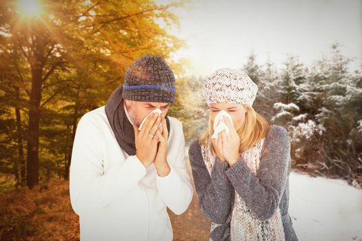 Couple sneezing in tissue against scenic shot of narrow road along forest