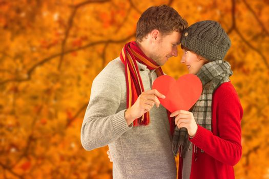 Couple holding a red heart against autumn scene