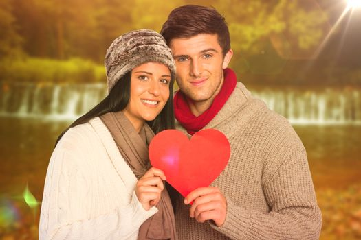 Young couple smiling holding red heart against autumn scene