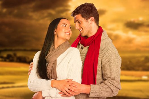 Young couple smiling and hugging against country scene