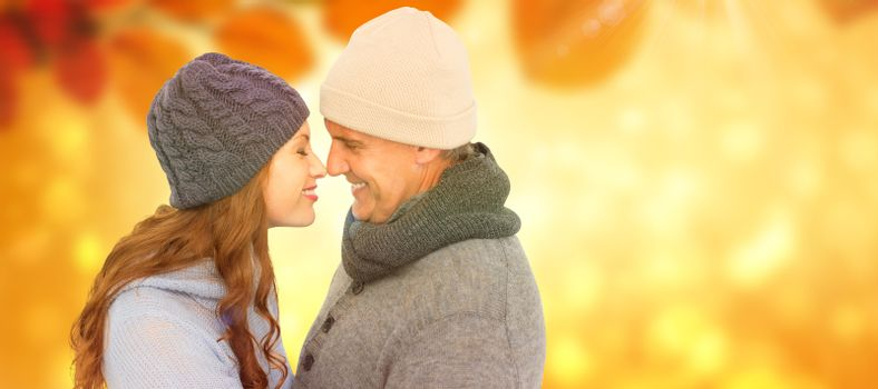 Couple in warm clothing facing each other against autumn scene