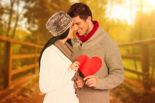 Young couple smiling and hugging against autumn scene