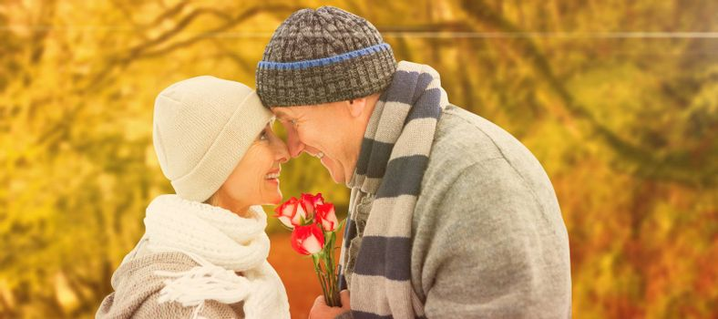 Happy mature couple in winter clothes with roses against peaceful autumn scene in forest