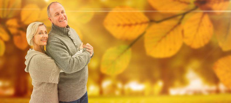 Happy mature couple in winter clothes against autumn scene