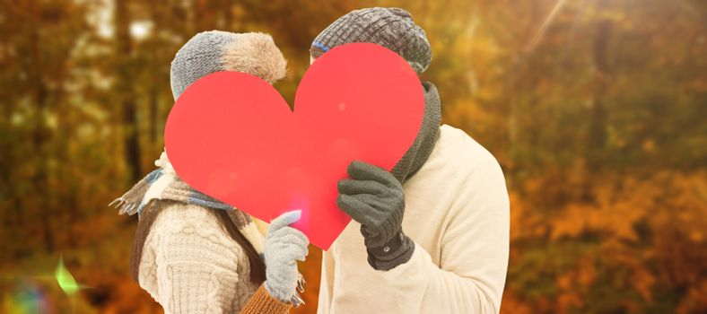 Attractive young couple in warm clothes holding red heart against autumn scene