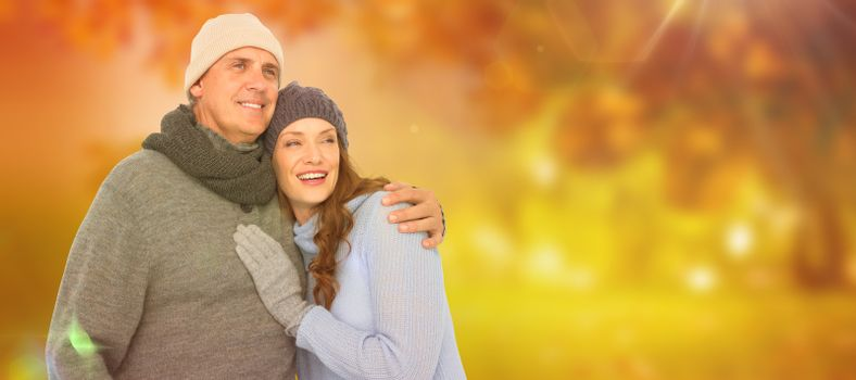 Couple in warm clothing embracing against autumn scene