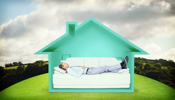 Businessman lying on sofa against hill with trees