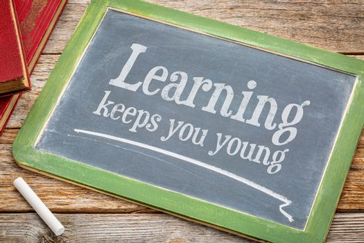 learning keeps you young - inspirationall words with a white chalk on a blackboard with a stack of books against rustic wooden table
