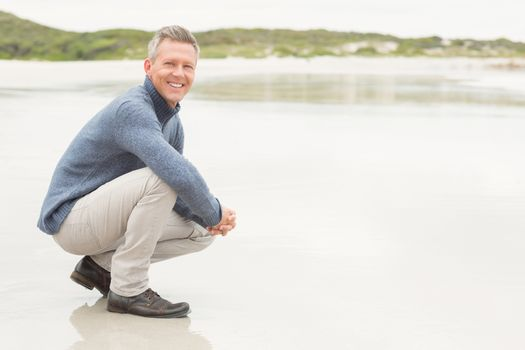 Man crouched down at the shore